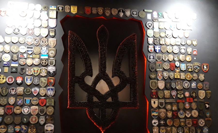 Herb Ukrainy wykonany z łusek, otoczony prawdziwymi naszywkami walczących batalionów. Pizza Veterano, prowadzona przez weteranów wojny w Donbasie