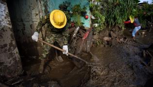 Żołnierz usuwa skutki lawiny błotnej w Kolumbii w roku 2017