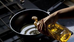 Kobieta nalewa olej do patelni
