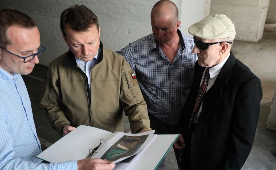Minister obrony narodowej Mariusz Błaszczak (2L), przewodnik Oleńczak Piotr (L) oraz były więzień Stanisław Łoniewski (P) z synem Piotrem (2P) zwiedzają Fort III Twierdzy Modlin w Pomiechówku