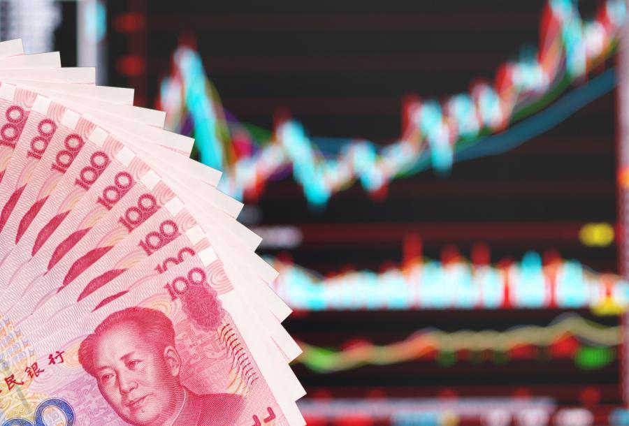 Chińskie juany na tle wykresu giełdowego