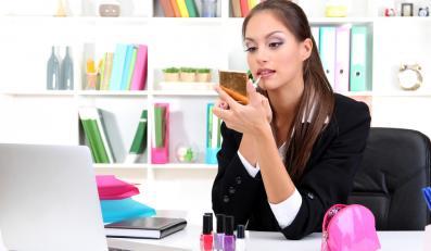 Kobieta przy biurku malująca usta