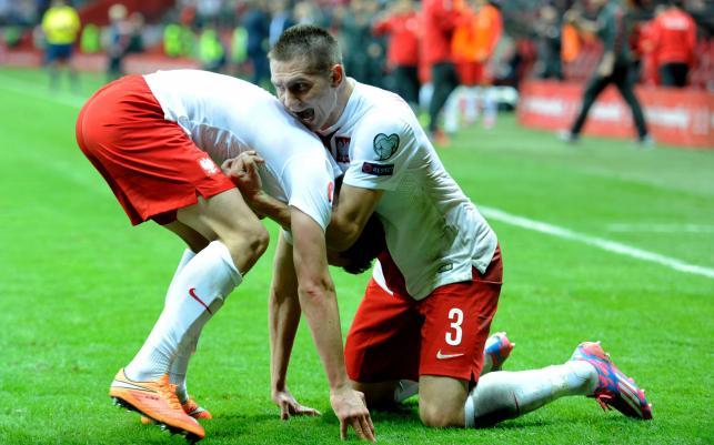 Polak Arkadiusz Milik (L) fetuje z Arturem Jędrzejczykiem (P) strzelenie bramki drużynie Szkocji na 2-2 podczas meczu eliminacyjnego piłkarskich mistrzostw Europy