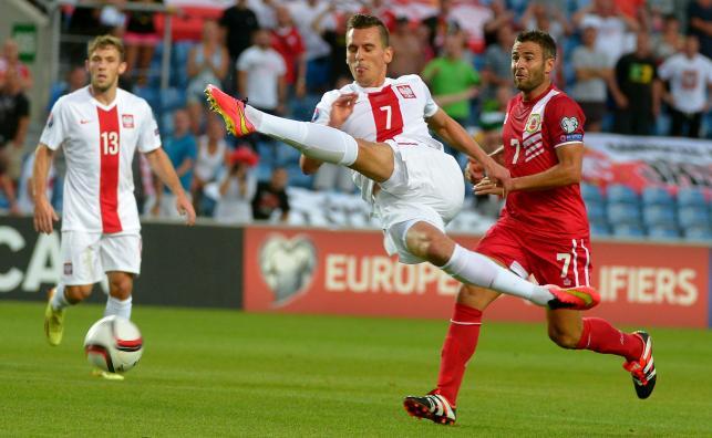 Polak Arkadiusz Milik (C) walczy o piłkę z Lee Casciaro (P) z Gibraltaru, w eliminacyjnym meczu piłkarskich mistrzostw Europy 2016 w portugalskim Faro