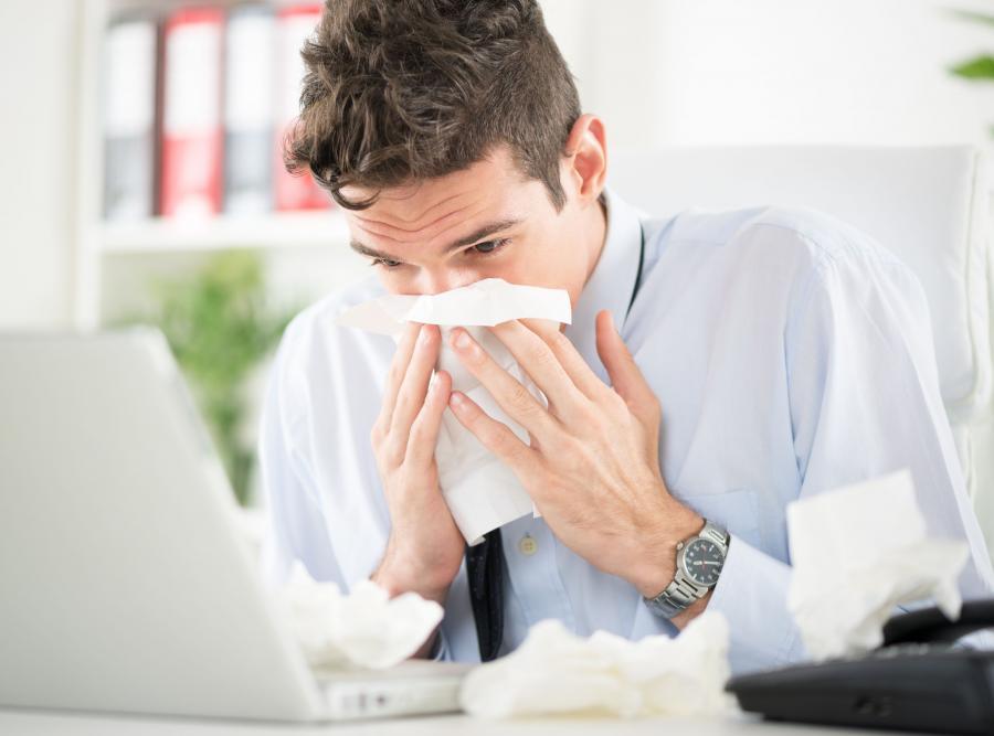 Mężczyzna przeziębiony w pracy