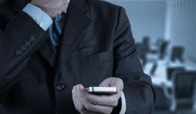 Mężczyzna z telefonem na tle sali konferencyjnej