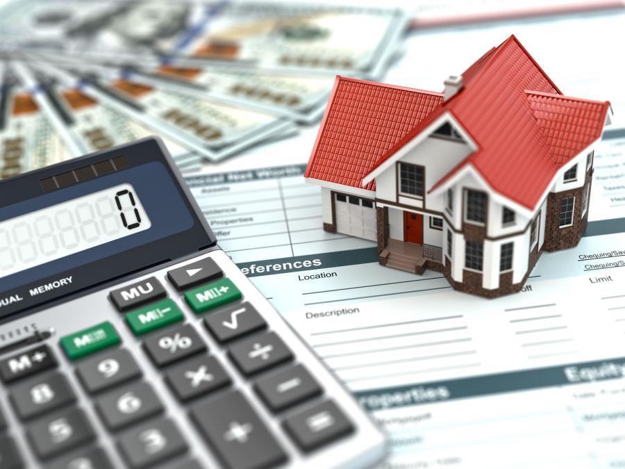 Kalkulator i makieta domu leżące na dokumentach