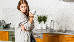 Kobieta z filiżanką herbaty w kuchni