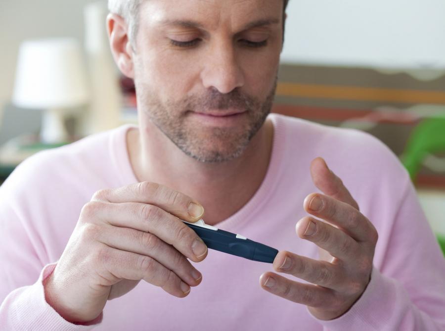 Mężczyzna bada poziom cukru glukometrem