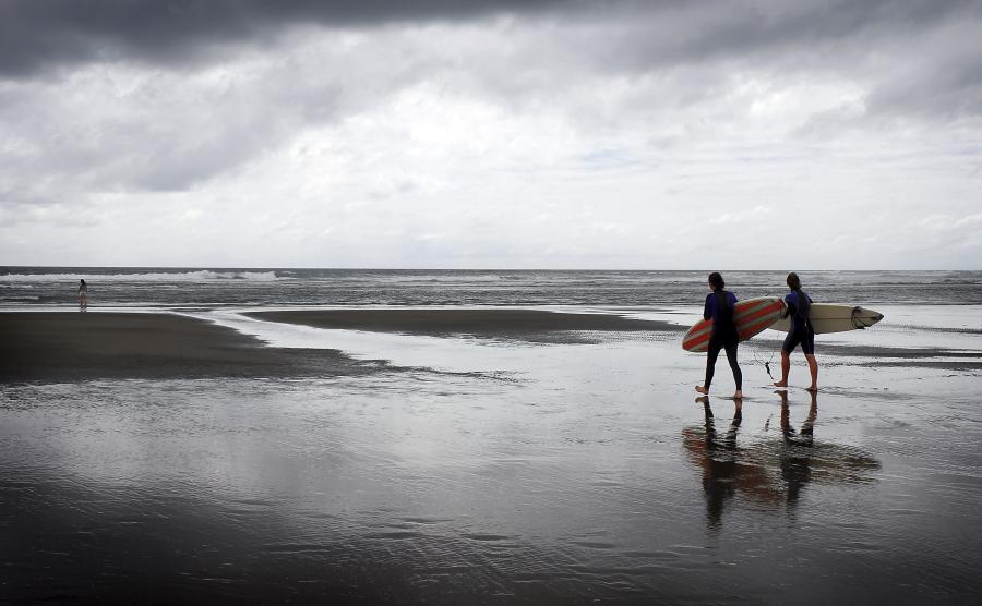 Surferzy na brzegu oceanu