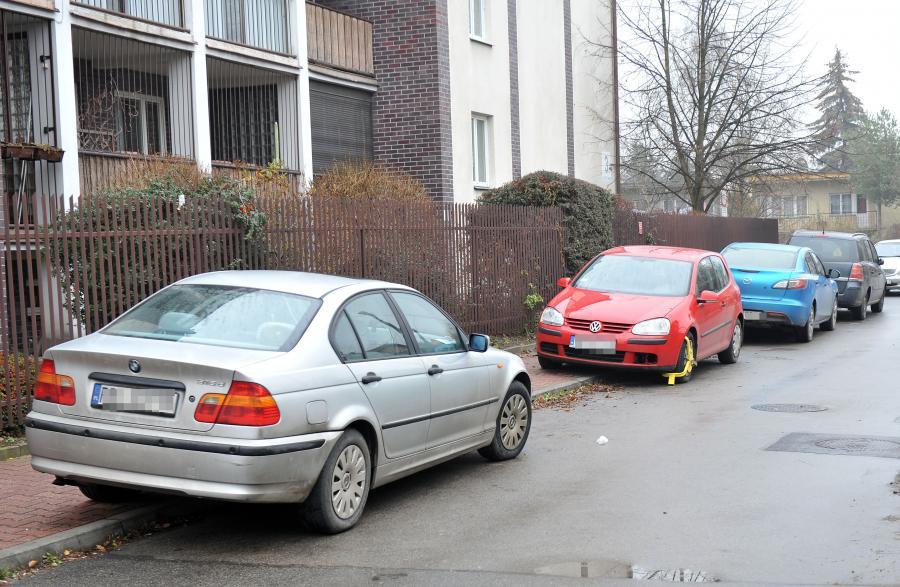 Źle zaparkowane samochody na ulicy Turystycznej w Krakowie. Wśród nich volkswagen golf prezydenta Andrzeja Dudy