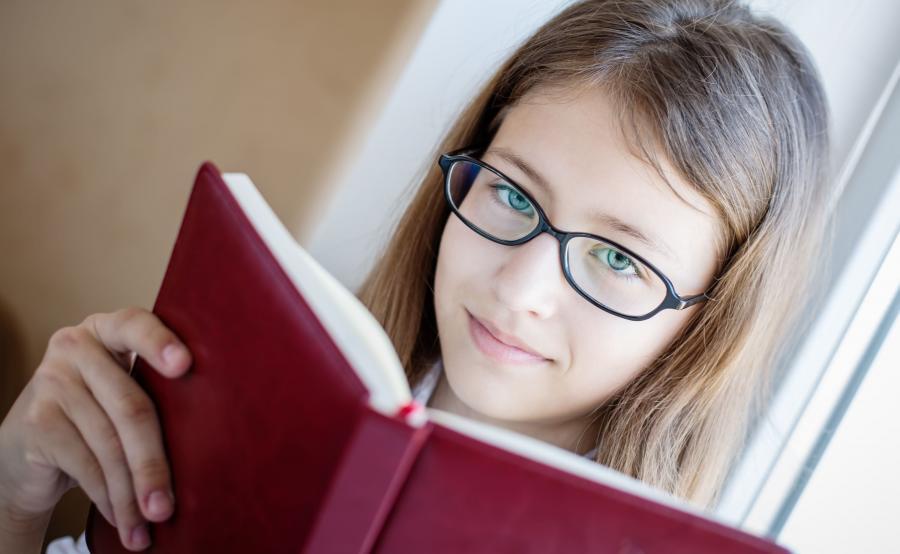 Dziewczynka w okularach czyta książkę