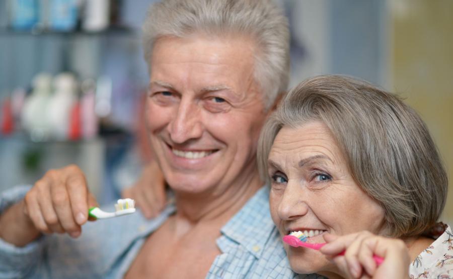 Starsza kobieta i starszy mężczyzna myją zęby
