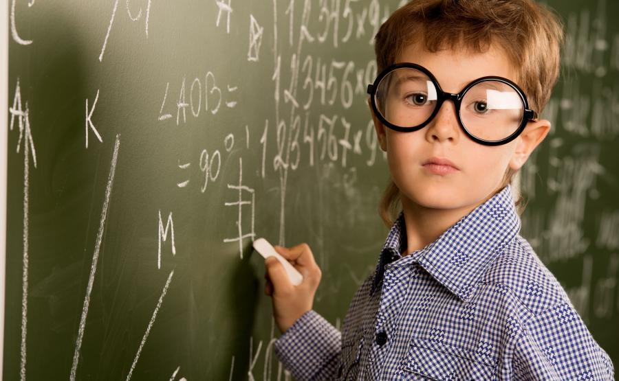 Chłopiec w okularach pisze na tablicy