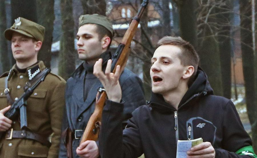 Ksiądz Jacek Międlar z opaską ONR na ramieniu przemawia przy pomniku żołnierza wyklętego Józefa Kuriasia \