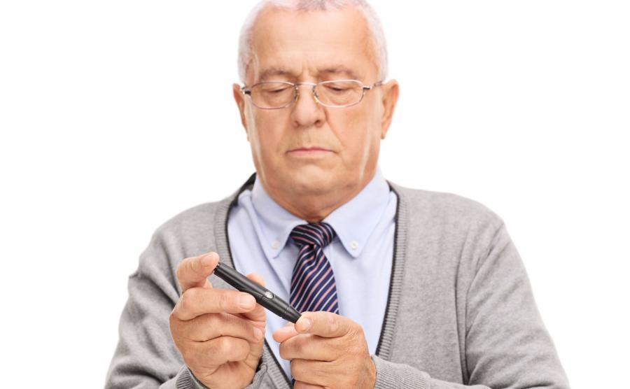 Starszy mężczyzna bada się glukometrem
